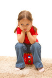 little girl sitting on a red plastic toy poster