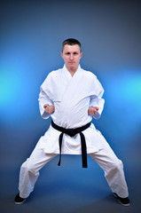 Young sporty karate man doing special exercise