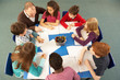 Overhead View Of Schoolchildren Working Together At Desk With Te