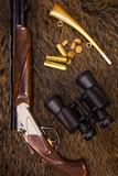shotgun, cartridges, binoculars and hunt on top of a boar skin poster