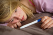 Depressed Teenage Girl Sitting In Bedroom With Pregnancy Test