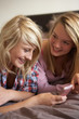 Two Teenage Girls Lying On Bed With Mobile Phone