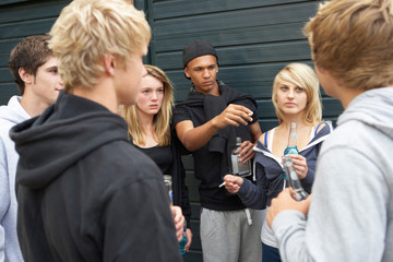 Group Of Threatening Teenagers Hanging Out Together Outside Drin