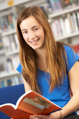 Female Teenage Student In Library Reading Book