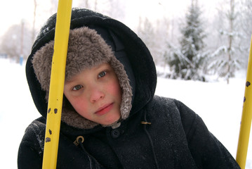 Sad boy on swing in winter