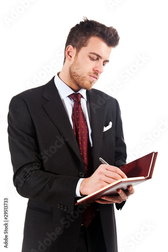 Businessman in black suit writing on agenda isolated on white