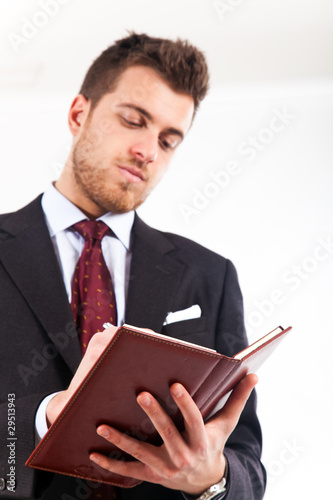 Portrait of a businessman writing on agenda in his office