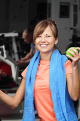 Woman with apple in fitness club