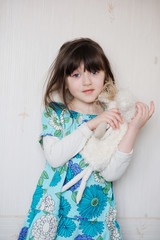 Adorable little girl in bright blue dress hugs her toy angel