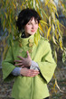 beautiful girl in the green coat in the branches of willow autum
