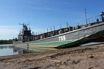 Transport military barge at the river bank against a blue sky
