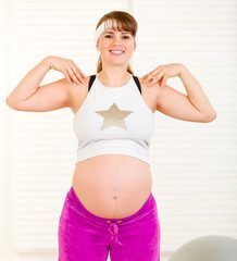 Smiling beautiful pregnant woman doing exercise at living room.
