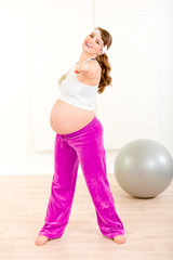 Smiling beautiful pregnant female doing exercise at living room.