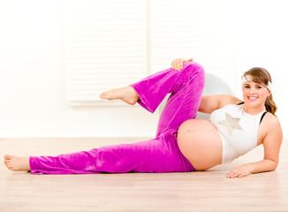 Smiling beautiful pregnant woman doing aerobics exercise