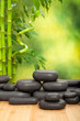 Black spa stones on green bamboo background