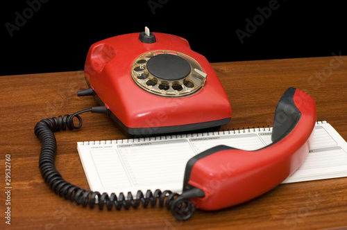 Red phone on a wooden table