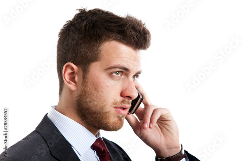 Businessman talking at the phone isolated on white