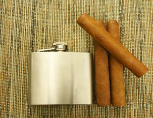 Close up of  cigars and hip flask