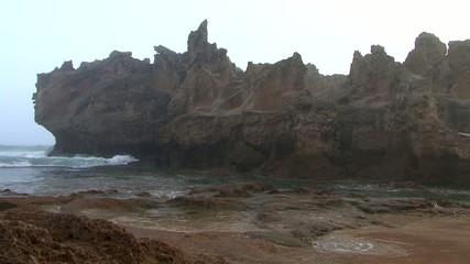 big waves breaking around a huge rock in the ocean