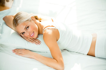 Young happy smiling woman waking up at bedroom