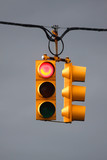Red traffic light with overcast sky background poster