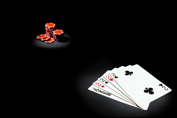 Red gaming chips and cards on black background