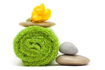 Yellow flower, green towel and river stones - harmony spa concep
