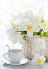 white tulips in a basket and cup of tea