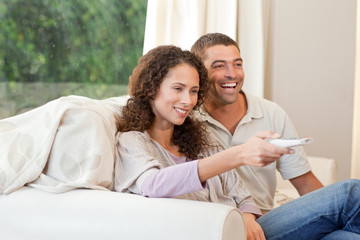 Couple watching tv in their living room at home