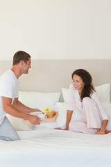 Man bringing the breakfast to his wife in bed