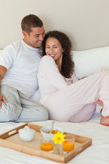 Couple having breakfast in their bed at home