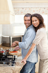Woman hugging her husband while he is cooking