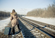 Teen girl with a suitcase near the railways at winter time