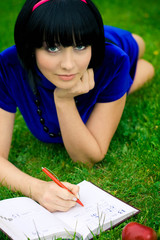 Young beautiful woman lays on green field with book
