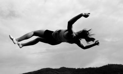 female gymnast jumping in sky