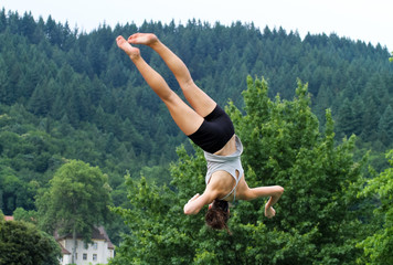 female gymnast doing somersault with spin in front of forest