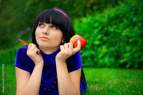 Young beautiful woman lays on green field with apple