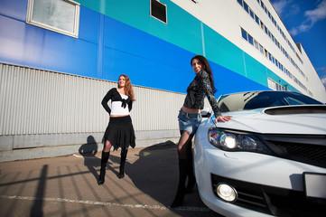 Two beautiful girls friend and stylish white sports car