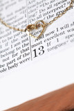 Gold necklace with heart on Bible open to 1st Corinthians 13 poster