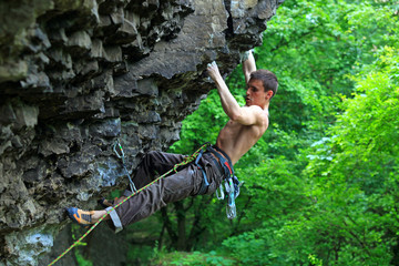 Rock climber preparing to the next movement, with bright green