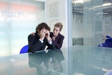 Businesswoman comforting colleague in conference room