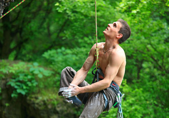 Tired rock climber hanging on rope
