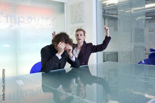 Cheering businesswoman next to sad businessman