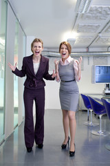 Two businesswomen screaming in office