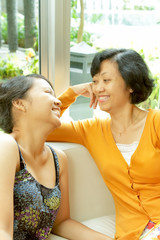 Happy conversation between ethnic mother and teenage daughter