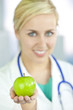 Smiling Woman Doctor in Hospital Holding Green Apple