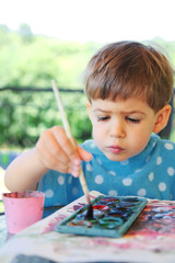 Little child paint with paintbrush outdoor