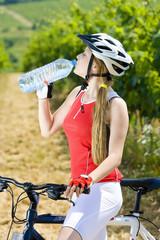 biker with bottle of water in vineyard