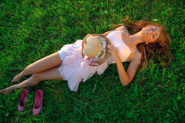 Sexy young girl lying down on grass