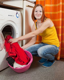 woman putting clothes into washing machine